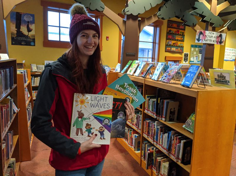 PMG PHOTO: BRITTANY ALLEN - Sami Stoecker is a Subaru Ambassador and donated four new STEM-related childrens books to the Sandy Public Library on Dec. 12 through a Subaru program.