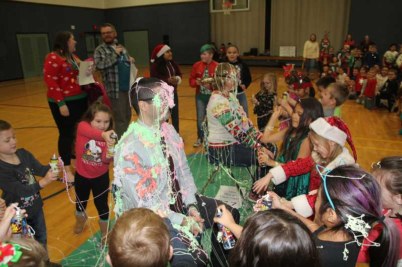 PMG PHOTO: JUSTIN MUCH - St. Mary Principal Katie Voss and Mount Angel Middle School Principal Jared Tiecke get a silly-spring saturation from kindergarteners as students celebrated the success of the school districts annual Toy and Food Drive.