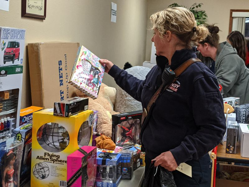PMG PHOTO: BRITTANY ALLEN - City Councilor and firefighter Laurie Smallwood searches for toys to complete a gift bag for a local family on Friday, Dec. 20.