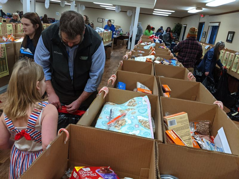 PMG PHOTO: BRITTANY ALLEN - Country Financials Cole Pritchard and his daughter Olivia participate in the Kiwanis Club Christmas Basket Program to compile gifts at St. Michaels Catholic Church.