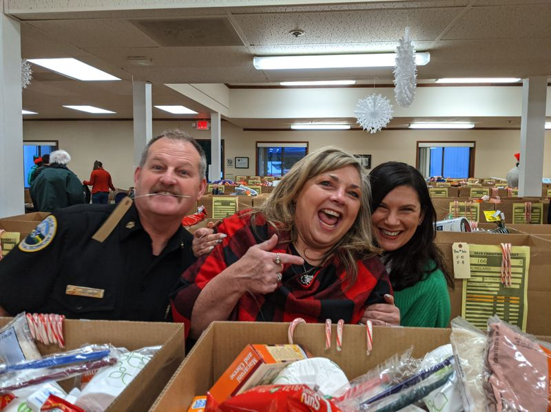 PMG PHOTO: BRITTANY ALLEN - Sandy Fire Chief Phil Schneider, Sandy Chamber Board Vice President Lisa Foster and Sandys Helping Hands Founder Machel Heldstab were among the many volunteers who took time out of their morning Friday to help with the Kiwanis Clubs Christmas Basket Program.