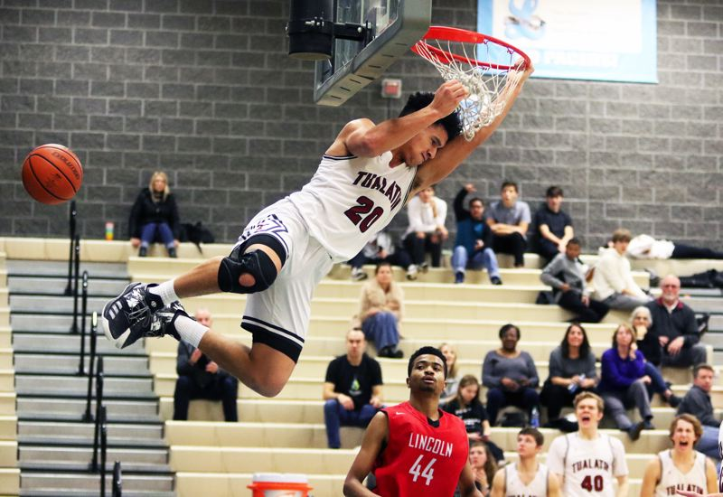 PMG PHOTO: DAN BROOD - Tualatin High School senior John Miller slams down his third dunk of the game during the Timberwolves' 62-41 win over Lincoln during play Friday at the Lakeside Tournament at Lakeridge High School.