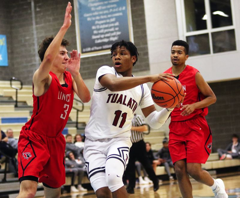 PMG PHOTO: DAN BROOD - Tualatin High School sophomore Malik Ross (11) looks to drive to the basket against Lincoln senir Mike Fortner during the Wolves' 62-41 victory over the Cardinals on Friday.