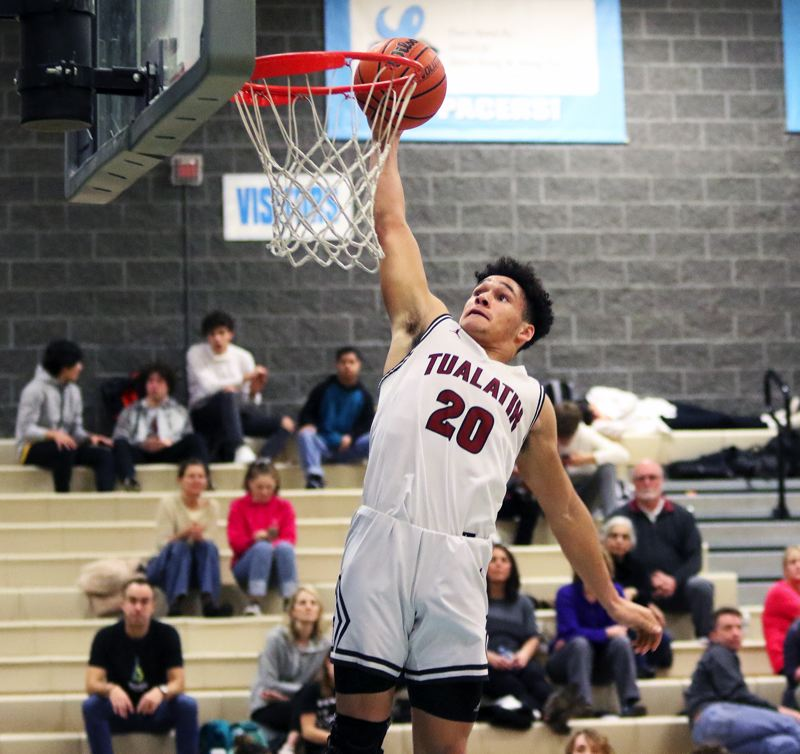 PMG PHOTO: DAN BROOD - Tualatin HIgh School senior John Miller goes up for his second of three dunks during the Timberwolves' 62-41 win over Lincoln on Friday.