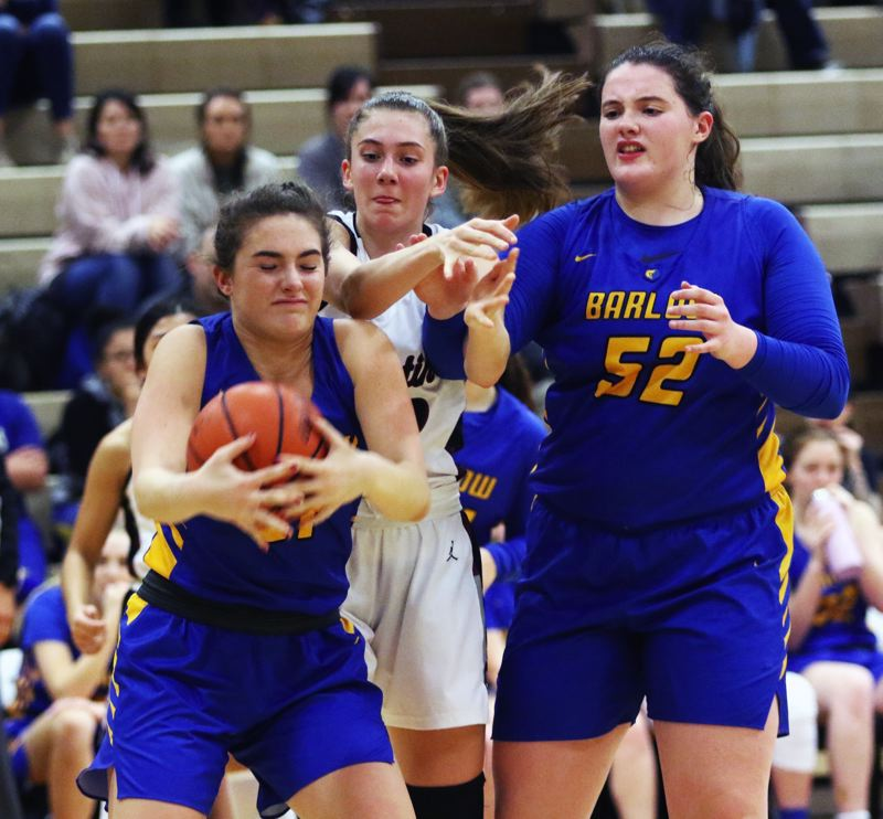 PMG PHOTO: DAN BROOD - Barlow High School senior Emory Miller (left) grabs the ball in front of Tualatin junior Natalie Lathrop (center) and Barlow senior Libby Mathis during Friday's game.