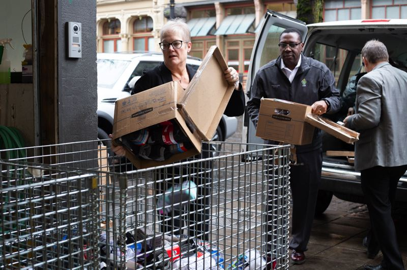 COURTESY: ADVENTIST HEALTH - Joyce Newmyer, left, president of Adventist Health's Pacific region, and Terry Johnsson, Adventist Health's vice president of mission integration, fill a bin with some of the more than 10,000 pairs of socks the health care provider collected for people who access services at Portland Rescue Mission.