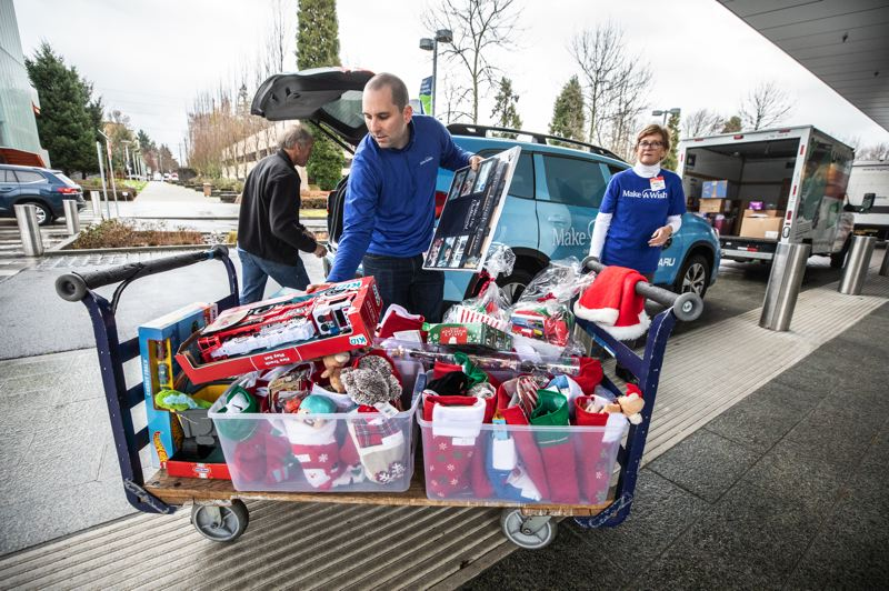 PMG PHOTO: JONATHAN HOUSE - Fletcher Johnson, development manager with Make-A-Wish Oregon, helps unload toys collected by Portland-area Subaru dealers during their Stock the Storefront campaign. The toys were destined for Holiday Magic pop-up shops for young patients at Randall and Doernbecher children's hospitals.