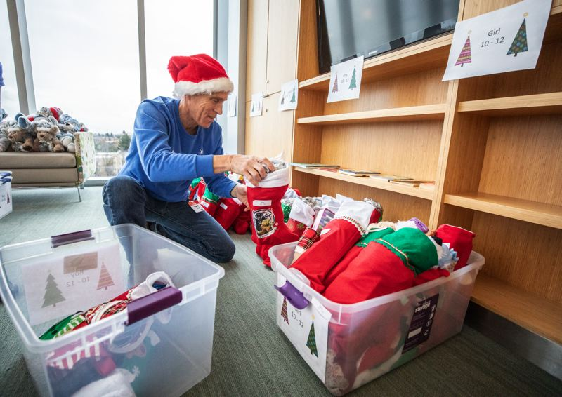 PMG PHOTO: JONATHAN HOUSE - A volunteer prepares to stock stockings at a holiday shop at Randall Children's Hospital. The shops, set up by Make-A-Wish Oregon, provide an opportunity for young patients at Randall and Doernbecher's children's hospitals to pick out gifts for themselves and their family members.