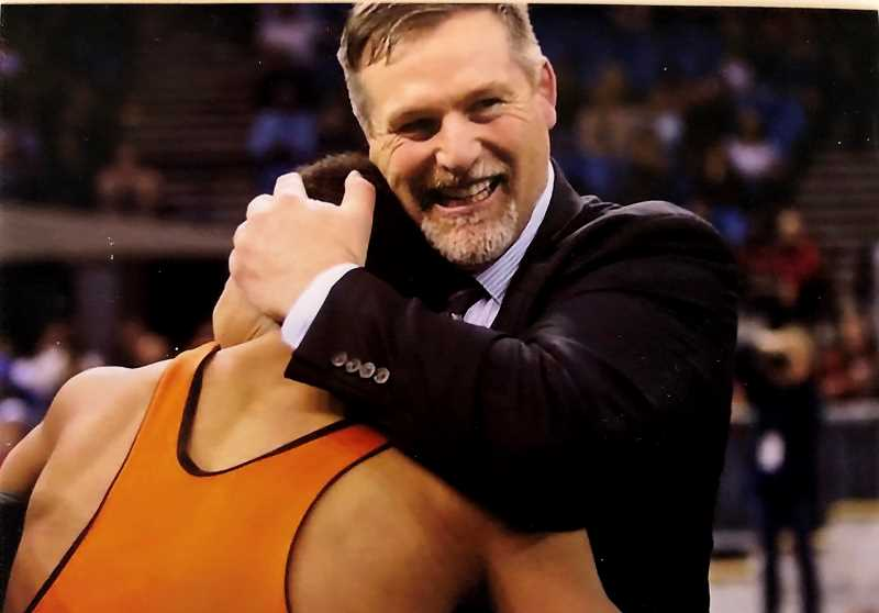 SUBMITTED PHOTO - Coach J.D. Alley hugs a wrestler after yet another individual state title.