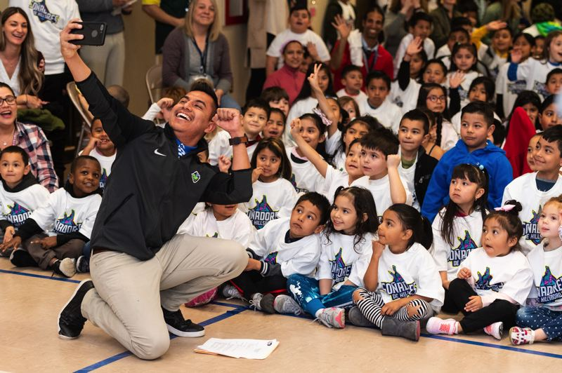 PMG PHOTO: CHRISTOPHER OERTELL - Latino outreach coordiantor Ivan Hernandez takes a selfie with students as the Hillsboro Hops revealed their alternate name and uniforms, the Sonadores de Hillsboro, during a school assembly at W.L. Henry Elementary School on Monday, March 18.