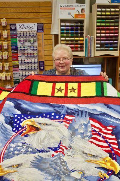 PMG PHOTO: CHRISTOPHER KEIZUR - Lynda Lutz, the NW Oregon State Coordinator for Quilts of Valor, shows off a finished quilt.