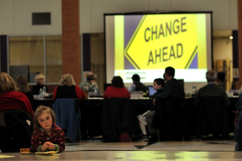 PMG FILE PHOTO - Gabby Kobrowski, 4, keeps busy while her father, Amit, who is a social studies teacher at Sunset High School, listens to Beaverton School District Superintendent Jeff Rose's opening remarks at a 2012 budget committee meeting.