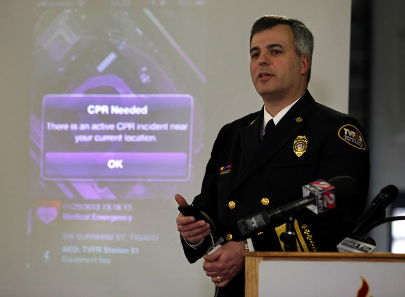 PMG FILE PHOTO - In 2013, then-Chief Mike Duyck of Tualatin Valley Fire & Rescue shows off the new PulsePoint app for smartphones, which alerts the public to nearby medical emergencies. The app has since been widely adopted by fire agencies across Oregon.