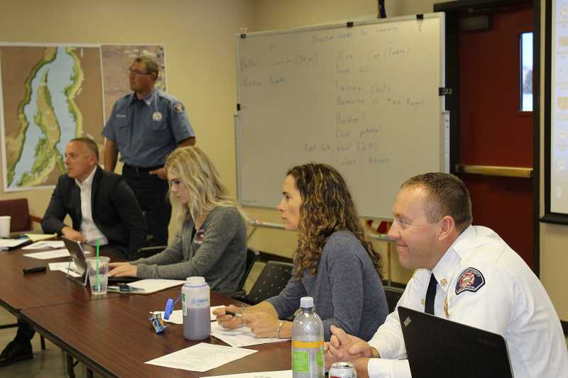 HOLLY GILL/MADRAS PIONEER - From right, Jefferson County Fire District Chief Brian Huff, moderator Katrina VanDis, administrative assistant LeeAnn Patton, Lt. Kirk Hagman, of JCFDD, standing, and Tim Gassner, attorney for the district, participate in a work session in September 2018.