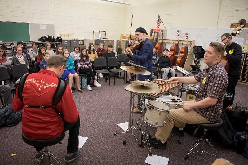 PMG PHOTO: JON HOUSE  - 3 Leg Torso performs to Lakeridge Middle School's music students recently at the school. Pictured from left to right; Courtney Von Drehle, accordion, Béla R. Balogh, violin, T.J. Arko, percussion, and Milo Fultz, bass.