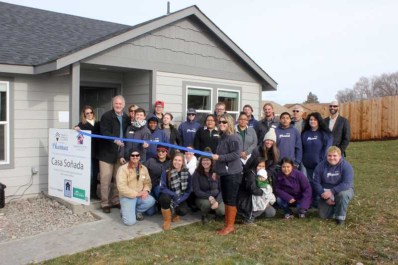 SUSAN MATHENY/MADRAS PIONEER - Housing Works Director David Brandt cuts the ribbon on house No. 6 in Madras, surrounded by YouthBuild crew members and partners in 2018.