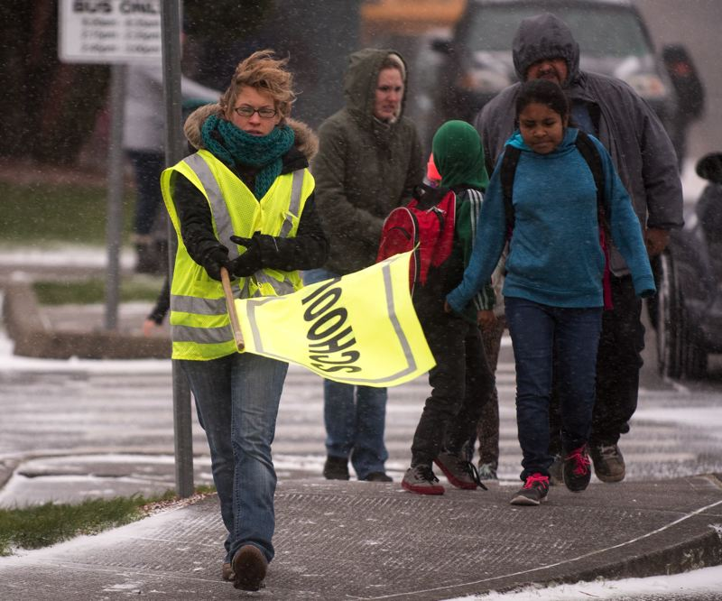 PMG FILE PHOTO - A crossing guard in Gresham leads parents and children across the street as snow comes down on Dec. 14, 2016.