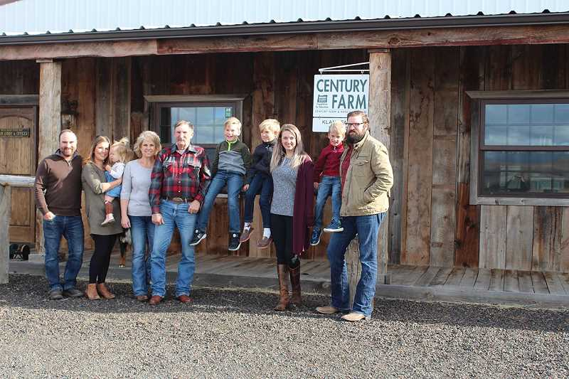 JANE AHERN/FOR THE PIONEER - The extended Klann family gathers for a photo next to the sign marking the Century Farm achievement. From left to right, they include Travis, Katie and Merit Ralls (23 months), Debbie and Brad Klann, Jet, 8, Silas, 7, Sally, Cash, 5, and Seth Klann., Madras Pioneer - News