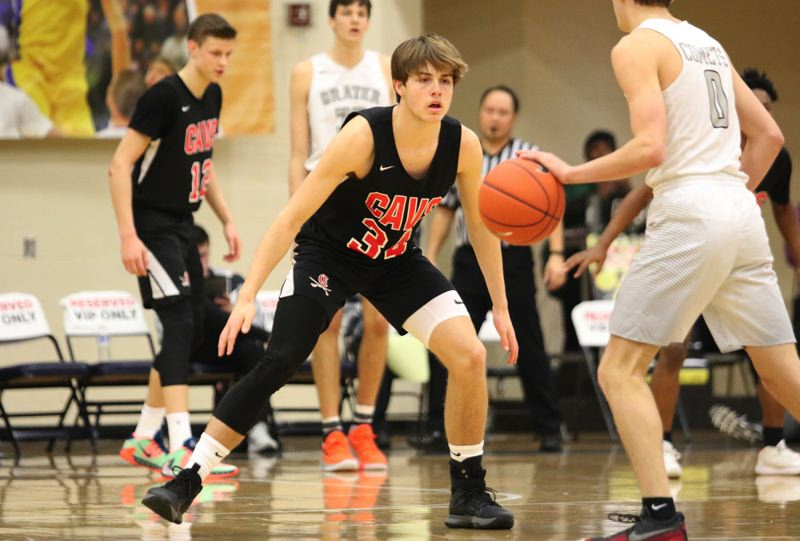 PMG PHOTO: JIM BESEDA - Clackamas' Ryan Lewis takes a defensive stand during the second half against Crater in Thursday's first round of the Les Schwab Invtational at Liberty High School in Hillsboro. Crater won 71-54.