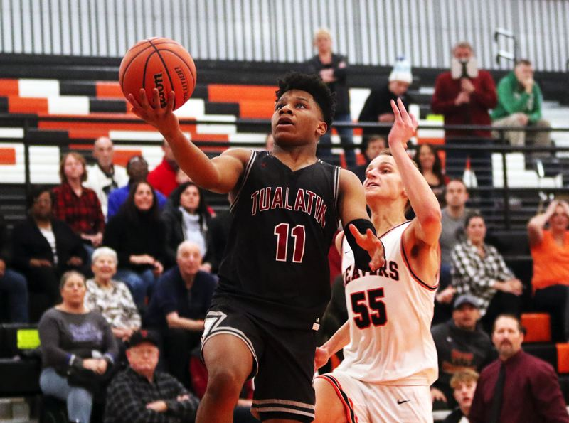 PMG PHOTO: DAN BROOD - Tualatin High School sophomore Malik Ross (11) goes up to the basket after coming up with a steal during Friday's non-league game at Beaverton. The Beavers won 55-52.