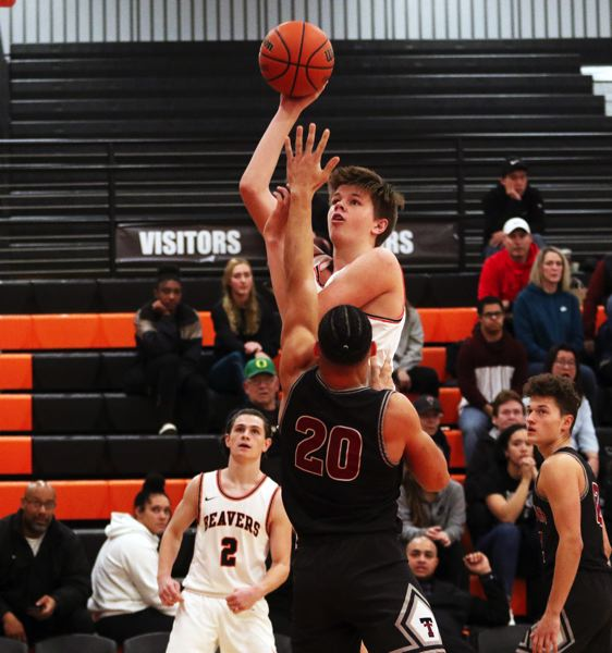 PMG PHOTO: DAN BROOD - Beaverton High School junior Dane Erikstrup looks to shoot over Tualatin senior John Miller during Friday's non-league game. Erikstrup led the Beavers with 17 points.