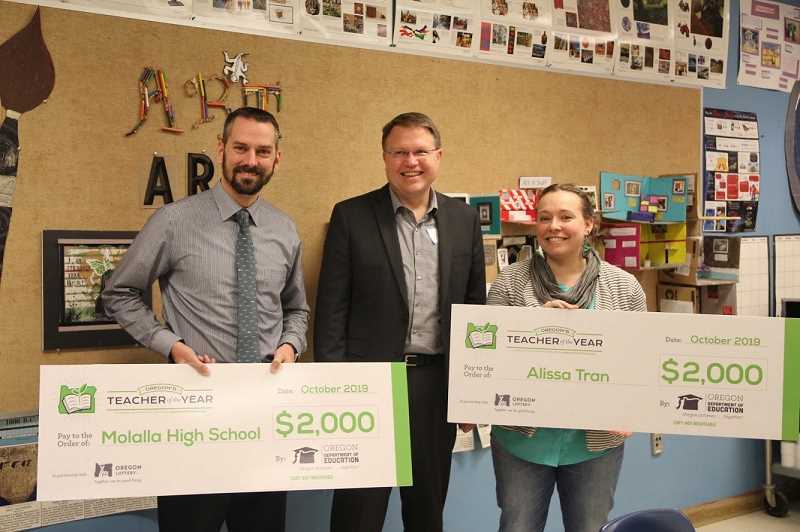 COURTESY PHOTO: JESSICA COY - Director of the Oregon Department of Education Colt Gill (center) presents $2,000 checks to Brad Berzinski (left) for Molalla High School and to Art Teacher Alissa Tran (right). The checks come because Tran was named as a finalist for Oregon Teacher of the Year.