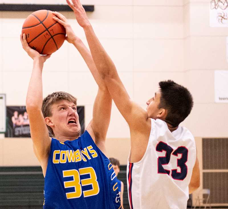 LON AUSTIN/CENTRAL OREGONIAN - Cayden Lowenbach goes up for a basket against the Juanita Rebels on Sunday. Lowenbach scored 17 points in the game as the Cowboys rolled to an easy 68-35 win over the Rebels.