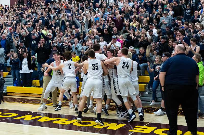 PMG PHOTO: CHRISTOPHER OERTELL - Banks players celebrate their state basketball championship in front of their fans moments after defeating Seaside 62-56, March 9 at Forest Grove High School.