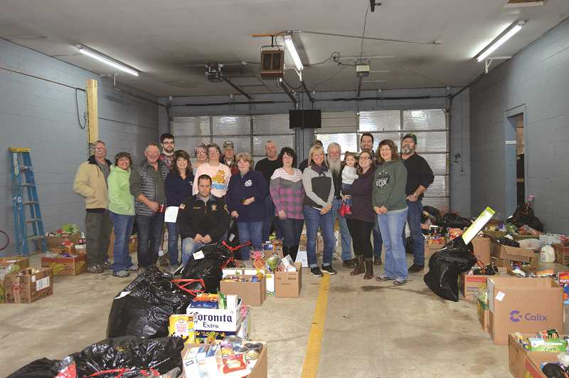 PMG PHOTO: CINDY FAMA - Christmas basket volunteers take a break during pickup day before Christmas.