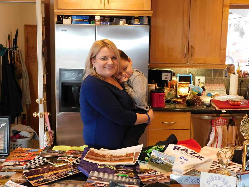 SUBMITTED PHOTO - Tina Jorgensen holds her grandson, Ezra Thomas, standing behind a collection of racing swag that was sent from all over the U.S. and Canada in support of the little boy who sustained a traumatic brain injury two years ago.