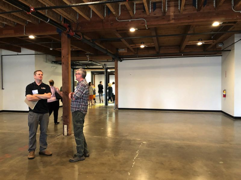 PMG FILE PHOTO - Lorentz Bruun project manager Erik Frame, left, stands in The Glass Lab. The former eastside glass manufacturing facility in  Portland's Innovation Quadrant has found new life as a space for innovators and creators.