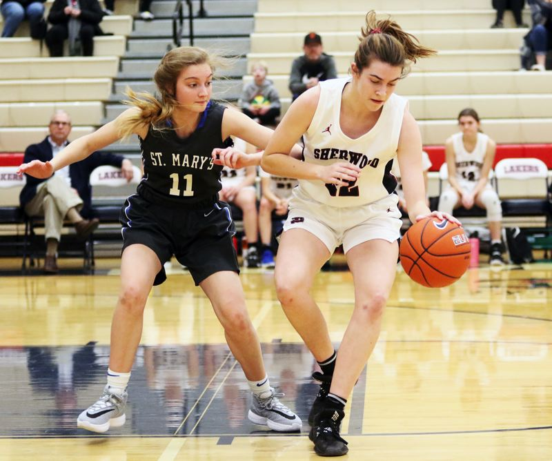 PMG PHOTO: DAN BROOD - Sherwood High School senior Julia Leitzinger (right) controls the ball against St. Mary's senior Jacque Jochum during the fourth-place game at the Nike Interstate Shootout.