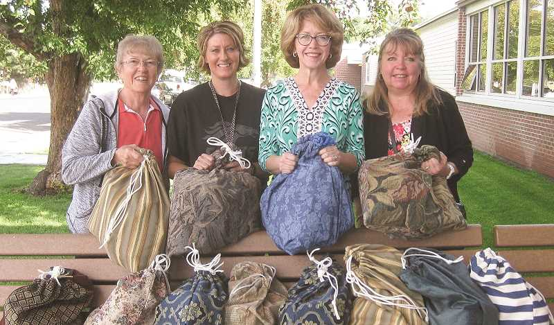 PHOTO SUBMITTED BY GLENDA JANSSEN  - Members of Prineville Presbyterian Church and the Crook County High School FAN advocate pause for a photo with several of the hand-sewn bags filled with toiletries for the Kits for Kids program. The bags are distributed by FAN advocates at the schools. Photo taken in 2018. From left: Glenda Janssen, Traci Peterson (FAN advocate for CCHS), Lori Desjardins and Stephanie Fahlgren.