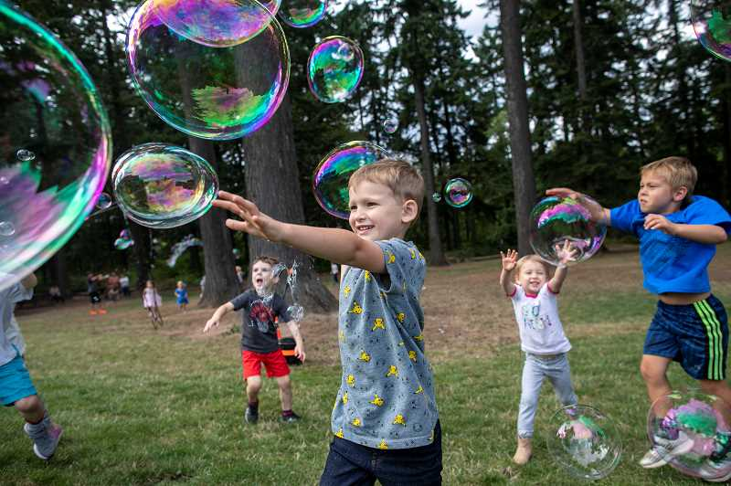 Ezra McCreith, 5, and his sister, Cora, 3, chase after bubbles during the Trillium Creek Primary's Backyard BBQ.