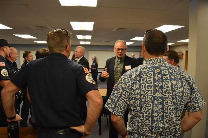 PMG FILE PHOTO - Fire Chief Dennis Hoke (facing, center) meets with guests at a meet-and-greet event in July, shortly before he was hired to replace retired Fire Chief Mike Greisen as the leader of Scappoose Fire District and Columbia River Fire and Rescue.
