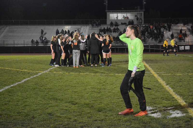 PMG PHOTO: STEVE BRANDON - The Scappoose Indians huddle moments after a late goal lifted them to a 2-1 victory over Putnam, as the Kingsmen goalkeeper heads back to their sideline. The win came on Senior Night, Oct. 24, at Scappoose High, and helped the Indians place second in league en route to a No. 5 state ranking.