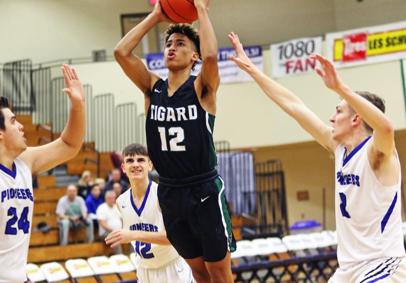PMG PHOTO: DAN BROOD - Tigard High School freshman Malik Brown (center) goes up for a shot between three Western Christian defenders during the Tigers' 85-78 victory on Thursday.