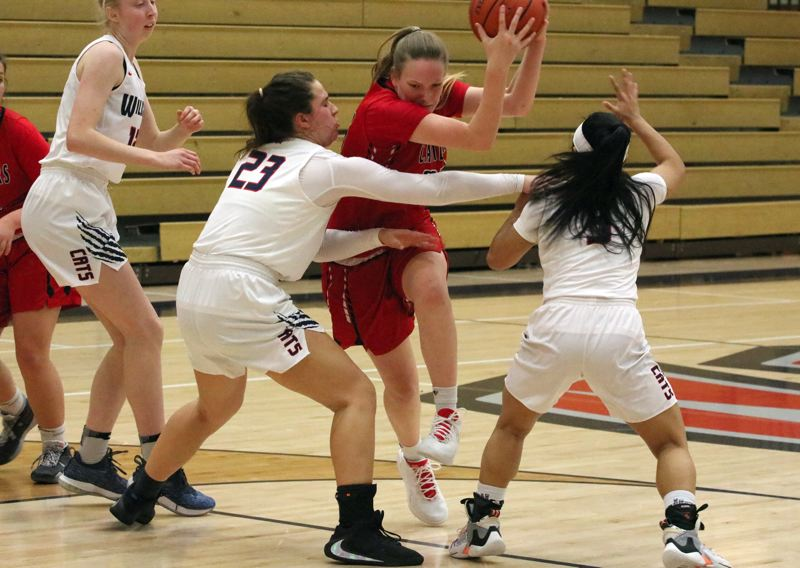 PMG PHOTO: JIM BESEDA - Clackamas forward Sydney Benedict tries to power her way to the basket between Westview defenders Afton Keeney (23) and Danielle Llamas (3) in the first half Friday.