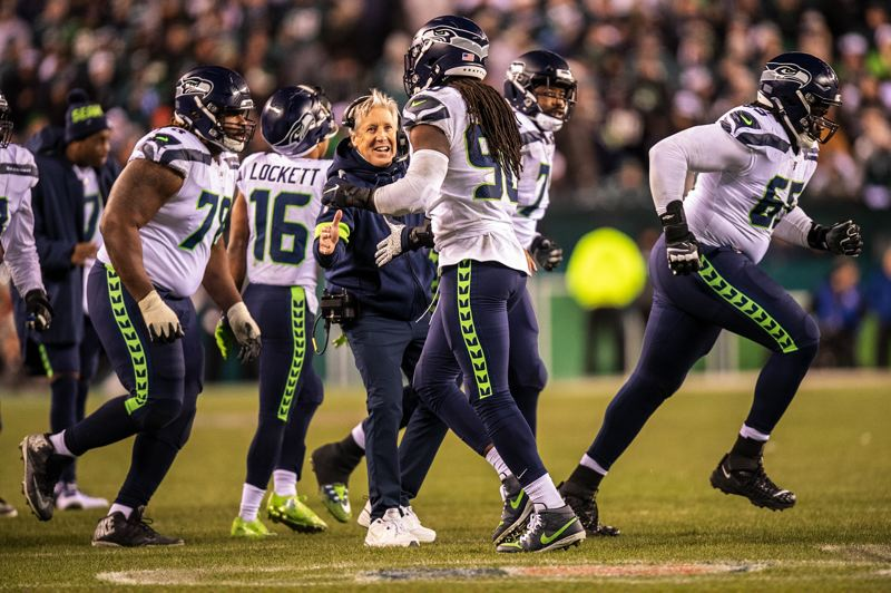 MICHAEL WORKMAN PHOTO - Seattle players and coach Pete Carroll celebrate as the Seahawks clear their first-round NFL playoff hurdle with a 17-9 victory at Philadelphia on Sunday.