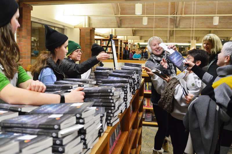 COURTESY PHOTO  - Volunteers from NCL Blue Heron Chapter help the library by distributing hundreds of free copies of the 2018 book paid for by the Friends of the Library.