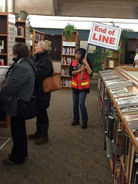 """COURTESY PHOTO - Volunteer Manami Kiriakedis holds the """"End of the Line"""" sign."""