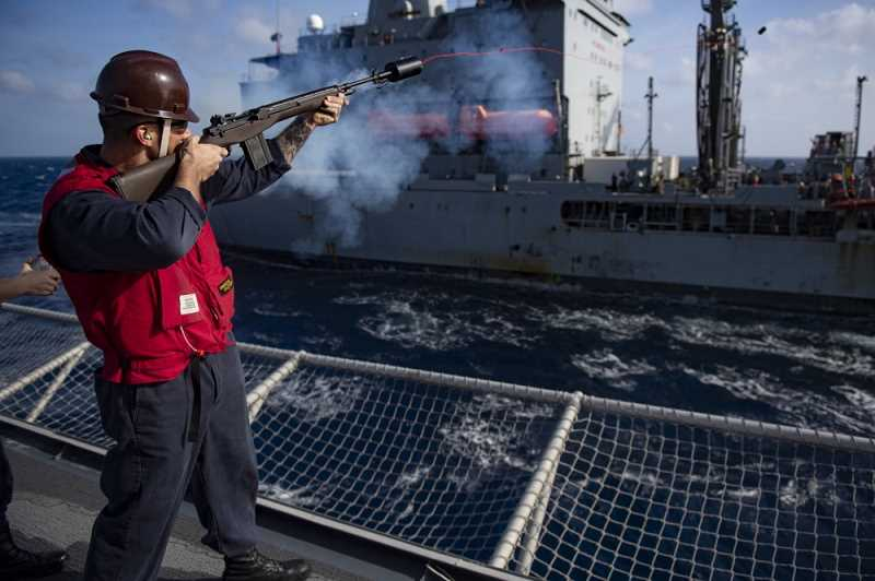 COURTESY PHOTO: JOSIAH J. KUNKLE - Gunner's Mate 1st Class Logan Buehner fires a line from the flight deck of the USS Gabrielle Giffords to the USNS John Ericsson during an underway replenishment.