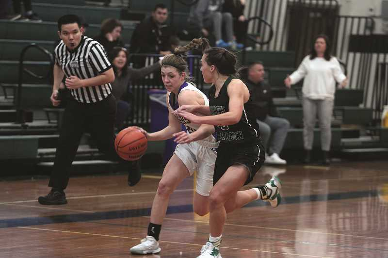 PMG PHOTO: PHIL HAWKINS - Gervais junior Katie Hanson advances the ball up court against pressure from North Marions Mya Hammack. The Cougars would go on to lose 31-28 to the Huskies for the teams first loss of the season.