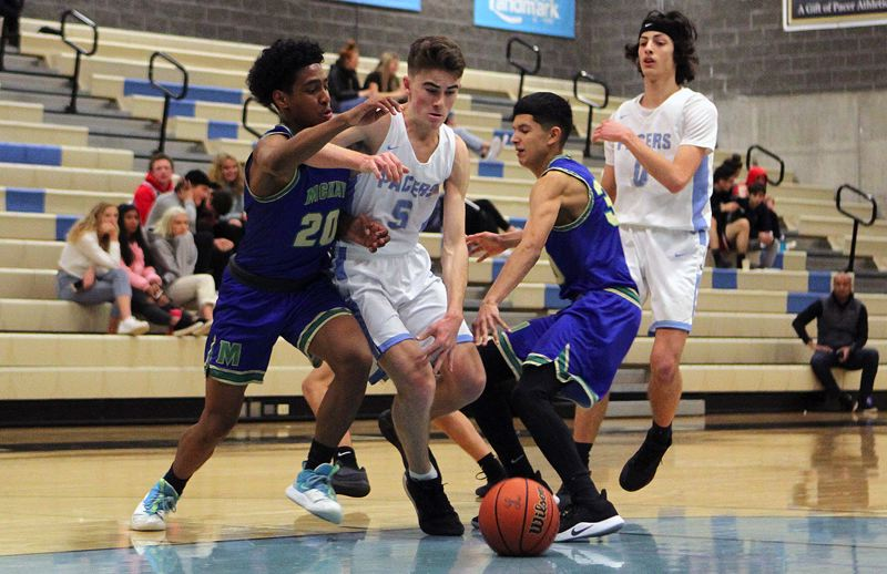 PMG PHOTO: MILES VANCE - Lakeridge junior guard Kobe Kruse splits two McKay defenders during his team's 69-47 non-league win over the Scots on Friday, Jan. 3, at Lakeridge High School.