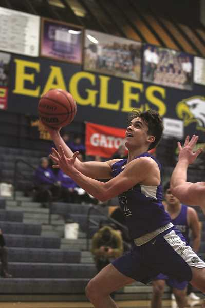PMG PHOTO: PHIL HAWKINS - Woodburn sophomore Tomas Veliz stretches out for a bucket in the first quarter of the Bulldogs 46-44 victory over Valley Catholic on Friday.