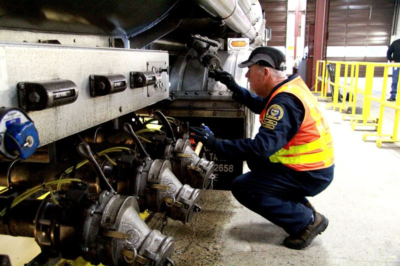 OREGON CAPITAL BUREAU/SAM STITES - ODOT inspector Don McCloskey checks valves on a truck hauling hazardous materials to make sure they're properly maintained.