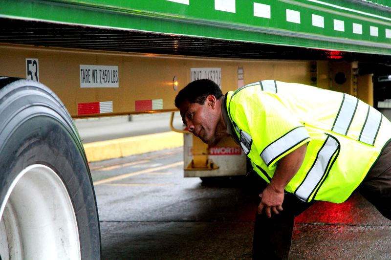 OREGON CAPITAL BUREAU/SAM STITES - Tom Avila inspects a tire shown by the tire anomaly detection system to have a problem. The pilot program implemented at the Woodburn port of entry helps prevent accidents by notifying drivers when there's an issue with a tire or axle, something that's not always obvious when they're out on the road.