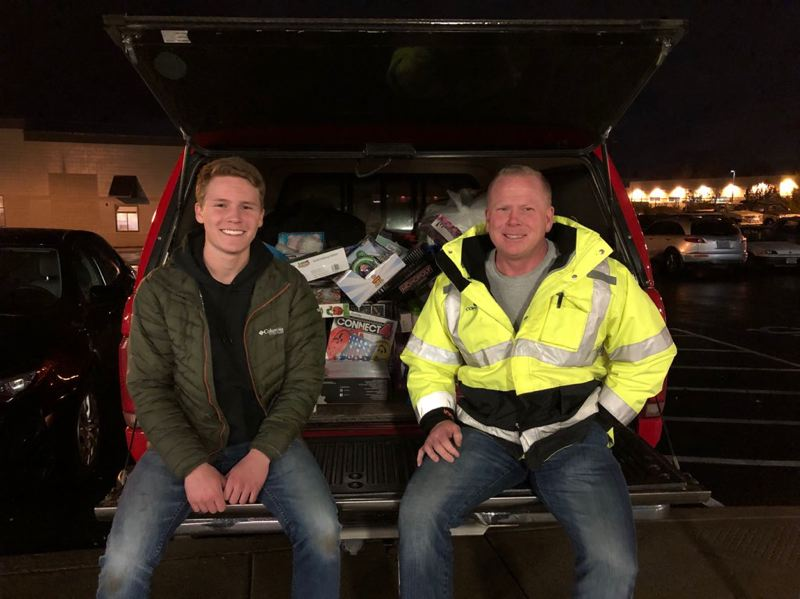COURTESY PHOTO: SCOTT BRAWNER  - Scott Brawner, right, sits with his son Jake on the Ford F250 pickup that was stolen from the McMenamins Edgefield parking lot last fall after a party for Coffman Excavation, Scotts employer. The truck turned up within days but without its contents of workplace and charitable gifts, some of which were returned to Shawn in December.