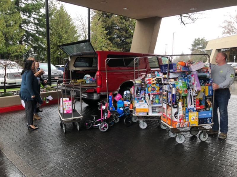 COURTESY PHOTO: SCOTT BRAWNER  - Scott Brawner, right, helps load his Ford pickup with employee and charitable gifts before a party for Oregon City-based Coffman Excavation in November. Some of the gifts were returned to Brawner after the truck was stolen after the employee gathering.