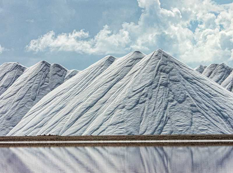LON AUSTIN/CENTRAL OREGONIAN - Salt is stored in giant piles next to shallow pools that are used to extract salt from sea water in Bonaire's salt mines, which are still thriving today.